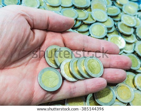 A hand holds some euro coins. Wealth, savings, business and economy concept - stock photo