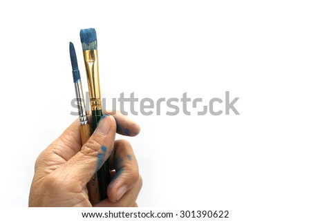 a hand holds two brushes in color blue