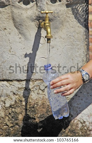 A hand is getting water in the faucet. - stock photo