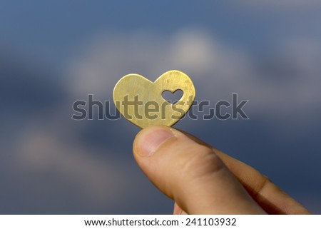 A hand is holding a beatiful bright heart shape with a small heart in it, on the backdrop of a blue sky with clouds. - stock photo