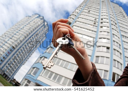 A hand is holding a key from the new home. A concept of real estate property agency