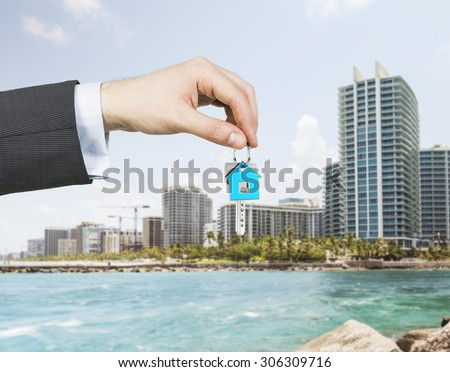 A hand is holding a key from the new home. A concept of real estate property agency. Miami cityscape on the background. - stock photo