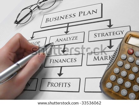 A hand is holding a pen and pointing at the word ANALYZE on a Business Plan diagram. There are some glasses and a calculator in the image. - stock photo