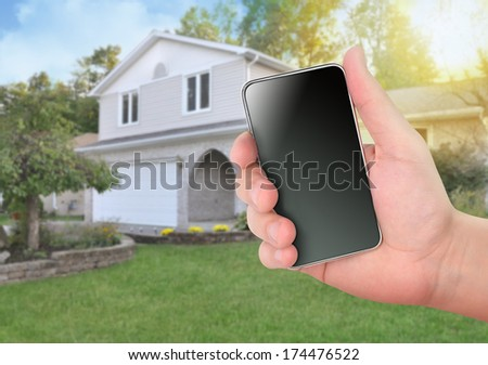 A hand is holding a smart phone in front of a house for a safety or control concept. The screen is blank to add your own message - stock photo