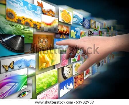 A hand is reaching out and touching a media gallery with photos on a black background. - stock photo