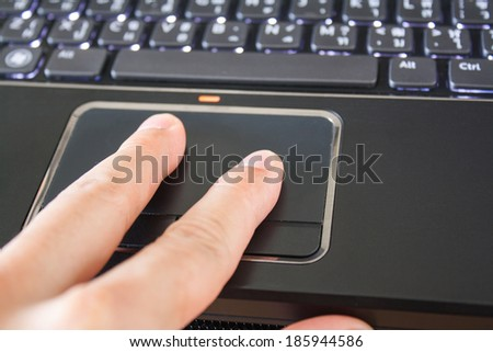 a hand is touching the laptop touchpad