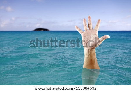 A hand of a drowning man stretch out from the deep blue sea. - stock photo