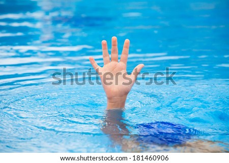 A hand of a drowning person stretching out of the water in a swimming pool asking for help. Stress concept. - stock photo