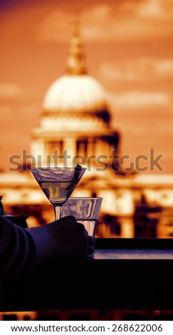 A hand of a woman with refreshing cocktail in martini glass with lemon twist and a digital tablet against a view from Tate Modern gallery's cafe on St Paul Cathedral. London, England. Toned photo. - stock photo