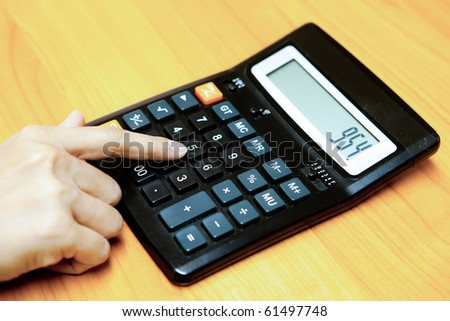 A hand of a women working on a calculator. - stock photo