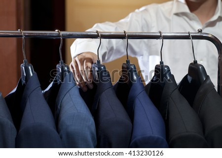 A hand of a young businessman choosing suit from the row of suits in the suit shop - stock photo