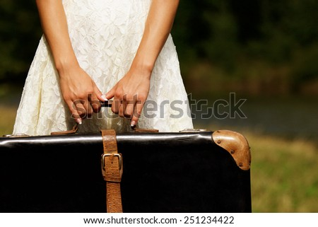 a hand of a young woman with a suitcase - stock photo