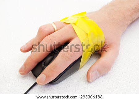A hand of men on a computer mouse tied with yellow adhesive tape. - stock photo