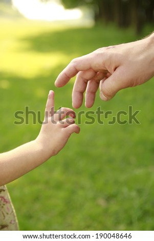 a hand of parent and child in nature