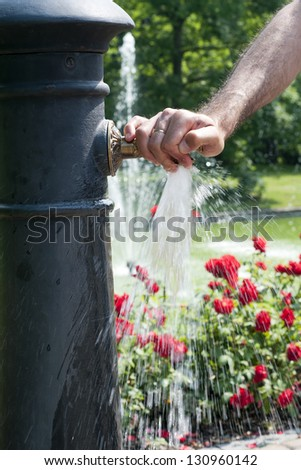 A  hand on a tap of a  water fountain with running water and a rose garden or a park in the background. - stock photo