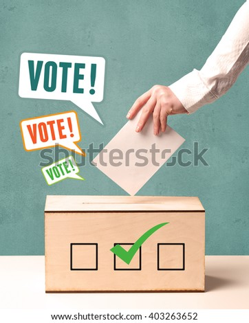A hand placing a voting slip into a ballot box - stock photo