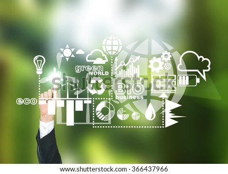 A hand pointing at symbols of alternative energy sources in green. Green background. Concept of clean environment. - stock photo