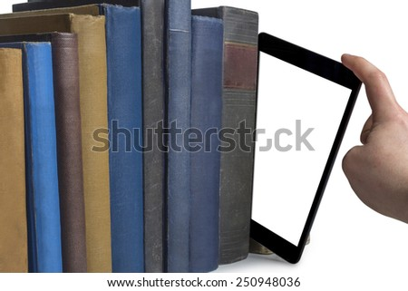a hand pulling a tablet computer out of a row of books isolated on white background - stock photo