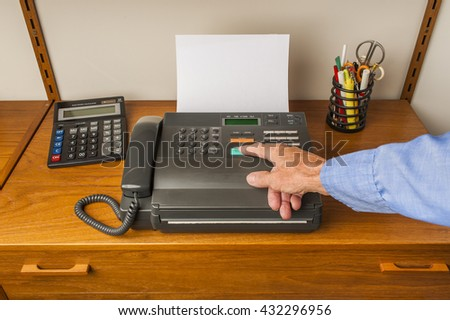 A hand pushing start button on an old retro style fax machine - stock photo