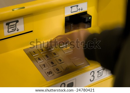 A hand touching the keyboard of the ATM - stock photo