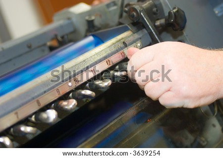 A hand twisting the knobs, adjusting and fine tuning the offset printing process - stock photo
