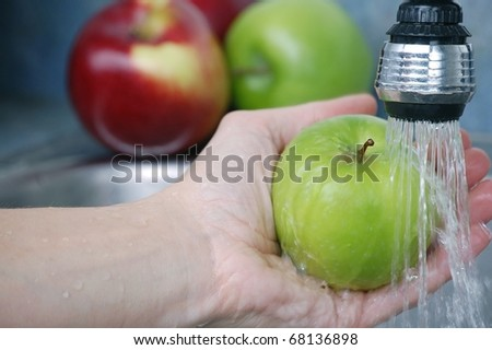 A Hand Washing a Delicious Green Granny Smith Apple in a Sink with More Apples in the Background - stock photo