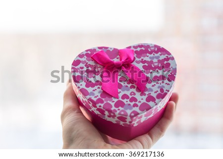 A hand with a box gift. Valentine's Day. Card - stock photo