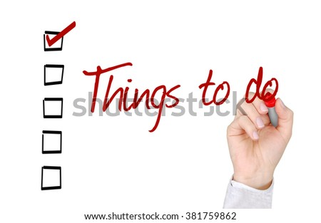 A hand with a marker writing 'Things to do'. - stock photo