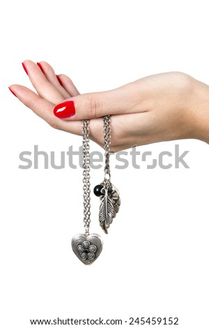 A hand with red nail holding a heart shaped necklace