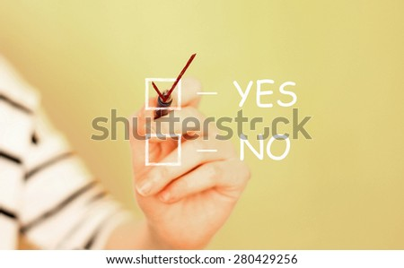 A hand writing a check mark yes no. - stock photo