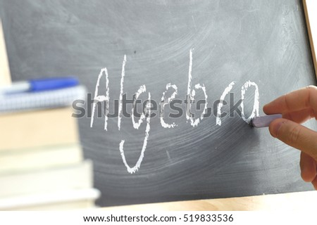 A hand writing in a blackboard during Algebra class in a school classroom.