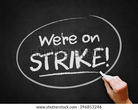 A hand writing 'We're on Strike!' on chalkboard. - stock photo