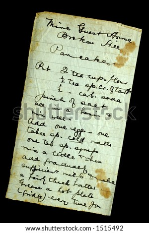 A hand-written recipe for pancakes, on stained and crumpled paper, isolated on black. Found in a 100-year old cookery book. - stock photo