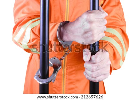 A handcuffed prisoner in jail holding bars isolated on white background with clipping path  - stock photo