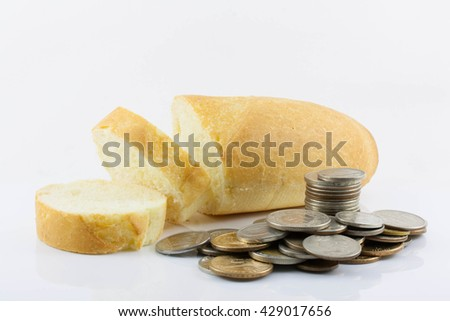 a handful of coins and sliced bread on white background. The increase in bread prices, the rising cost of bread, inflation, crisis, isolated - stock photo