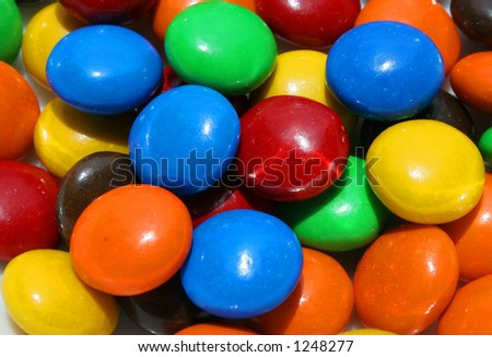 A handful of colorful candies with chocolate centers.