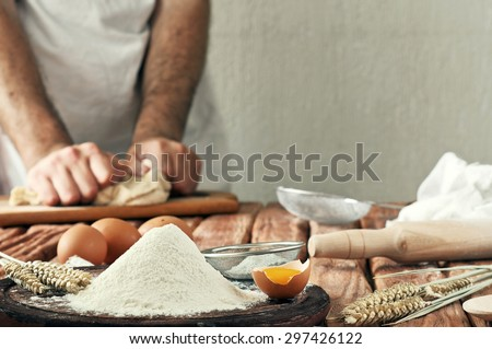 A handful of flour with egg on a rustic kitchen. Against the background of men's hands knead the dough. Ingredients for cooking flour products or dough (bread, muffins, pie, pizza dough). Copy space - stock photo