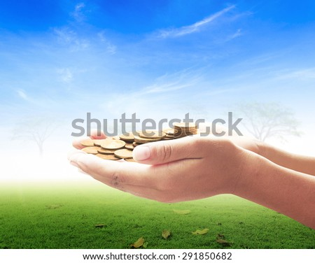 A handful of golden coins in the palm of a hand over beautiful nature background. Money coin concept. - stock photo