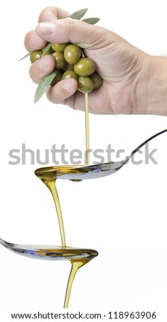 A handful of olives dropping olive oil into a spoon - stock photo