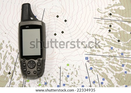 A handheld GPS unit sits on a topographical map.  The blank screen is ready for your text. - stock photo