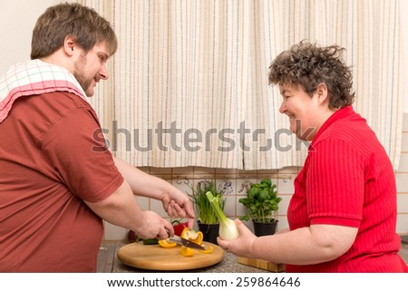 a handicapped woman and a young man in the kitchen - stock photo