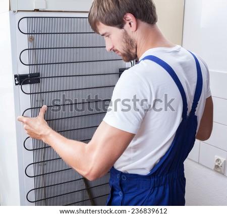 A handiman in work clothing repairing a refrigerator - stock photo