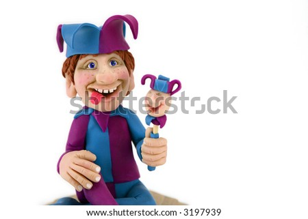A handmade polymer clay sculpture of a Jester holding a scepter.  I am the original artist who made the sculpture. He's against a white background. - stock photo