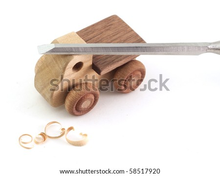 A handmade wooden truck with chisel and shavings - stock photo