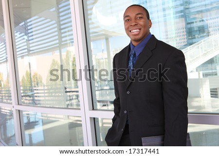 A handsome african american business man in front of company - stock photo
