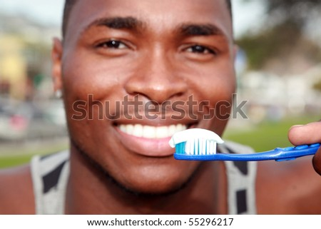 a handsome african american male is excited about brushing his teeth - stock photo