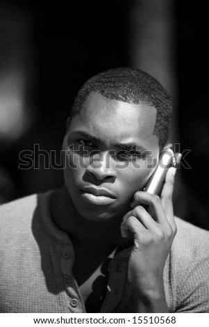 a handsome african american man talks on his cell phone in black and white