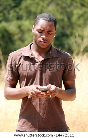 a handsome african american man thinks and responds while he text messages on his cell phone - stock photo