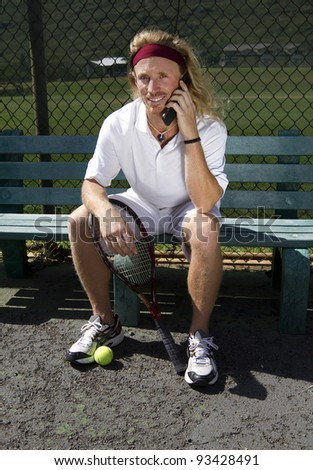 A handsome blonde tennis player sits on the sideline bench and talks on his cell phone - stock photo
