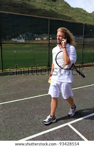 A handsome blonde tennis player talking on his cell phone on the court - stock photo